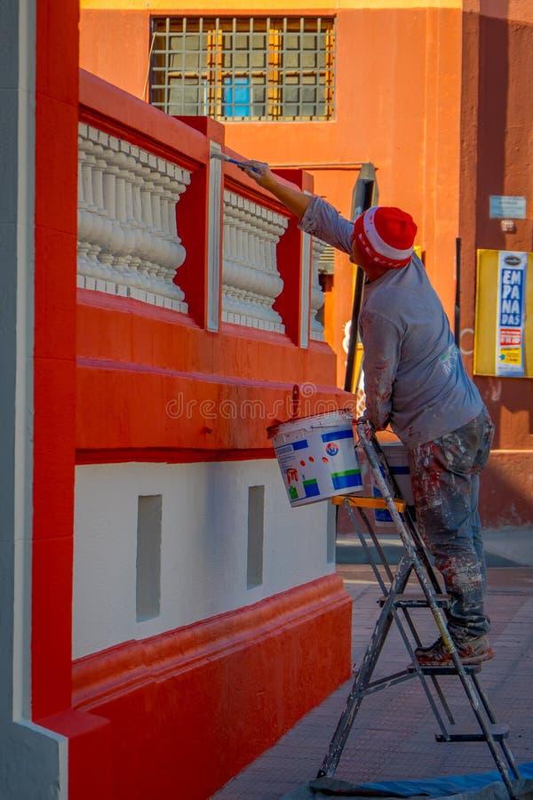 SANTIAGO CHILE - SEPTEMBER 13, 2018: Utomhus- sikt av den oidentifierade mannen som målar en husbyggnad med röd färg i arkivbild