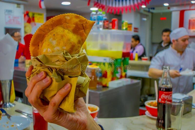 SANTIAGO CHILE, WRZESIEŃ, - 13, 2018: Zakończenie up selekcyjna ostrość mężczyzna ręka z chilijczykiem Empanada, piec ciasto obraz royalty free