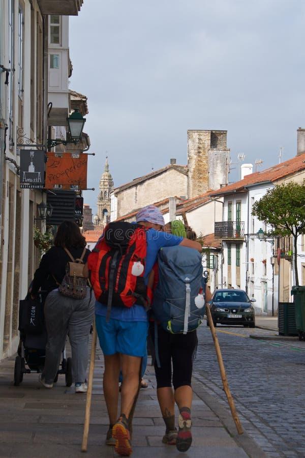 Santiago de Compostela, Spain - September 2018: Pilgrims of Camino de Santiago walking toward their destination through Santiago d royalty free stock photo