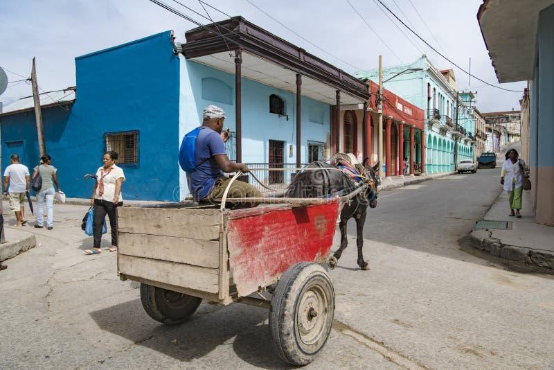 Santiago de Cuba, carro traído por caballo delante de casas coloridas imagen de archivo