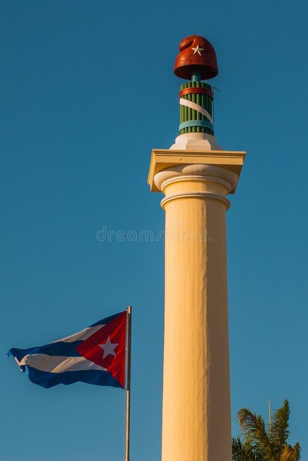 SANTIAGO DE CUBA KUBA: Kolonn av frihet på den Plaza de Marte fyrkanten Kubaflaggan framkallar på bakgrunden av himlen fotografering för bildbyråer
