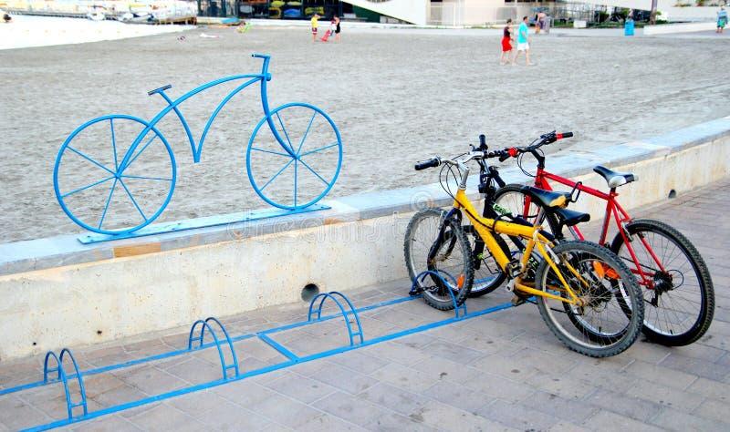 Santiago de la Ribera, Murcia, Spagna - 31 luglio 2018: Biciclette parcheggiate in uno scaffale della bici, segnato da una scultu immagine stock libera da diritti