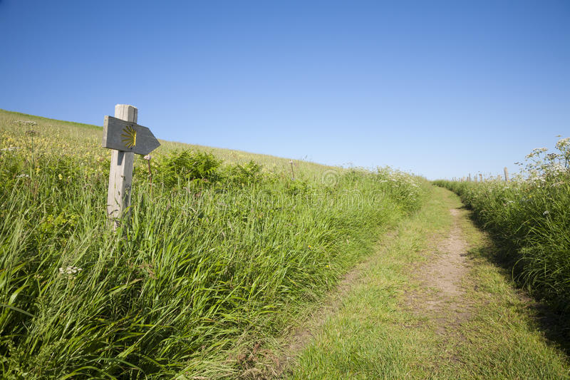 Santiago pilgrimage path. Rural path and wood signpost with public Middle Ages symbol of Camino de Santiago the biggest Christian pilgrimage route this in stock photos