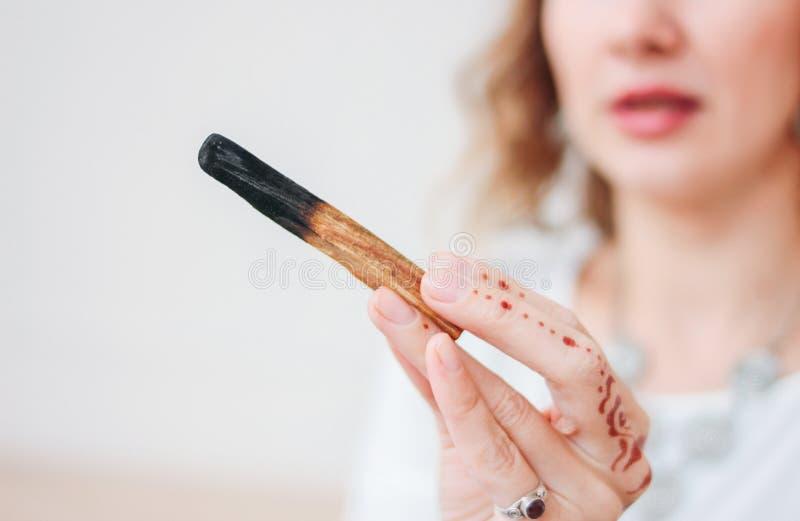 ??santo?Bursera graveolens 白肤金发的年轻女人藏品棍子圣洁木头,关闭 库存照片