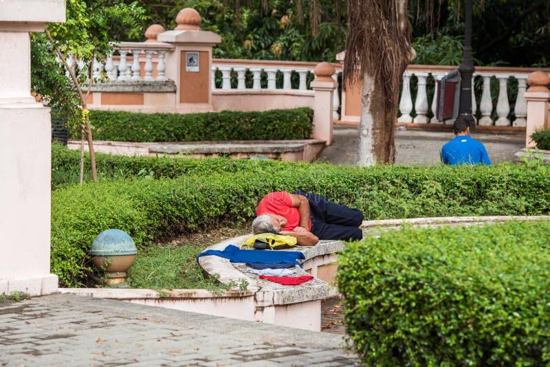SANTO DOMINGO, DOMINICAANSE REPUBLIEK - 8 AUGUSTUS, 2017: Een mens slaapt op een bank in een stadspark Exemplaarruimte voor tekst royalty-vrije stock afbeelding