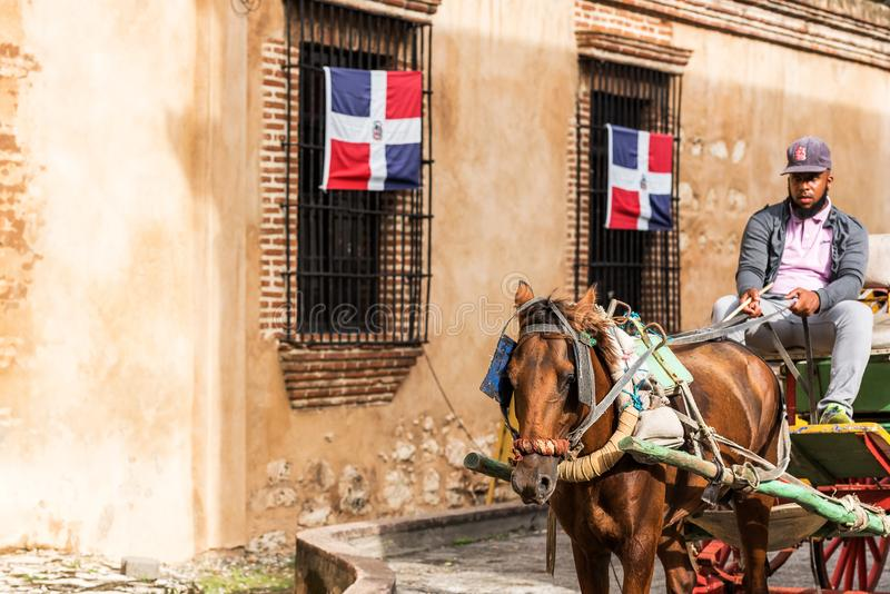 SANTO DOMINGO, DOMINICAN REPUBLIC - AUGUST 8, 2017: The coachman in a retro carriage on a city street. Copy space for text. SANTO DOMINGO, DOMINICAN REPUBLIC royalty free stock images
