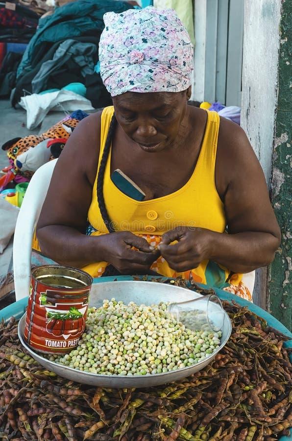 06-01-2019 Santo Domingo, Dominican Republic. black senior woman alone opening pods royalty free stock photos