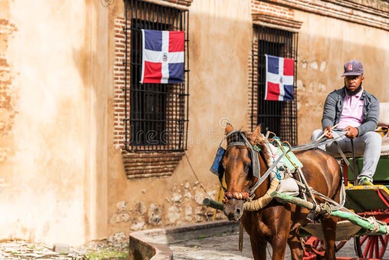 SANTO DOMINGO, DOMINIKANISCHE REPUBLIK - 8. AUGUST 2017: Der Kutscher in einem Retro- Wagen auf einer Stadtstraße Kopieren Sie Ra lizenzfreie stockbilder