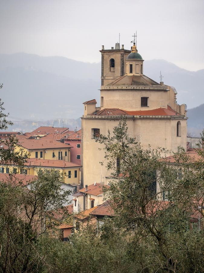 Santo Stefano Magra church and houses in Lunigiana area of Italy in La Spezia province. Vertical shot. Wintry day. Santo Stefano Magra church and houses in royalty free stock photography