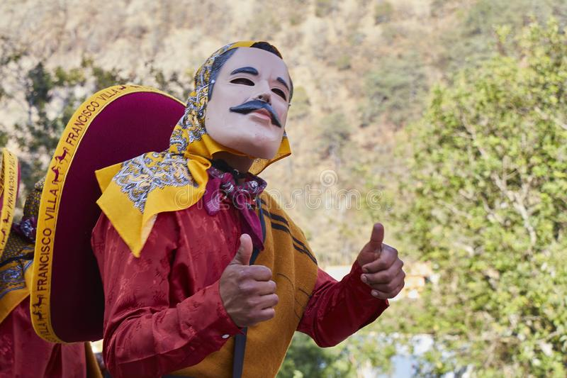 Person doing thumbs up, with mask with mustache, red dress and mexican. Santo Tomas Ocotepec, Oaxaca, Mexico, March 3, 2019: Person doing thumbs up, with mask stock photos