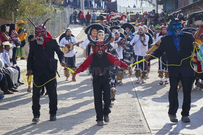 Santo Tomas Ocotepec Oaxaca, Mexico, mars 3, 2019: Tre maskeringar för röd jäkel för personer iklädda under en karneval i Mexico arkivfoton