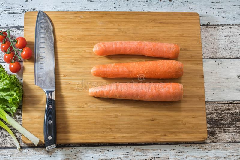 Santoku在一个切板的厨刀有新鲜蔬菜的:红萝卜、蕃茄、莴苣和葱在木背景 免版税图库摄影