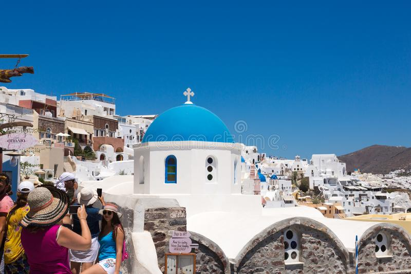 Santorini, Ελλάδα: Οι τουρίστες ανθρώπων κάνουν τις φωτογραφίες στον μπλε θόλο υποβάθρου της εκκλησίας στοκ φωτογραφία με δικαίωμα ελεύθερης χρήσης