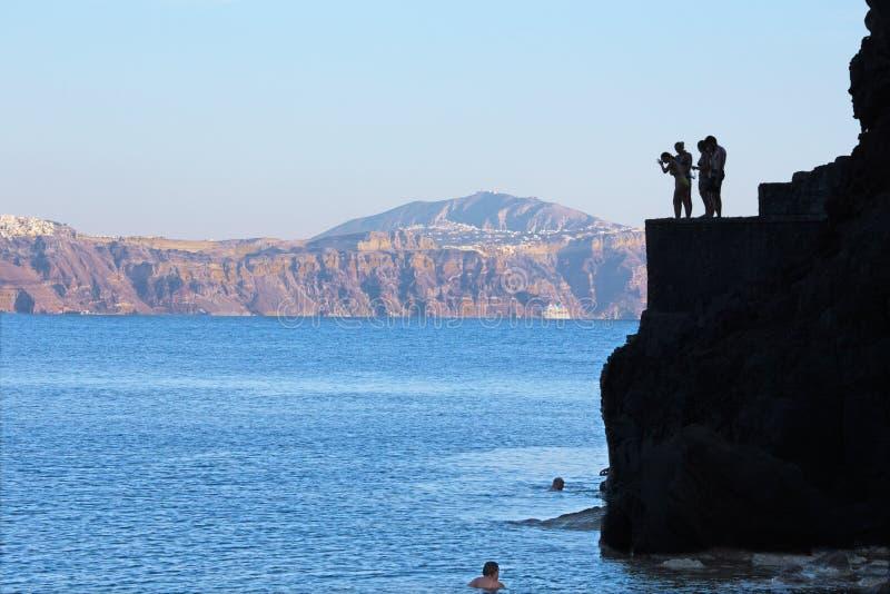 Santorini - молодые шлямбуры немногое на побережье под Oia стоковое изображение rf