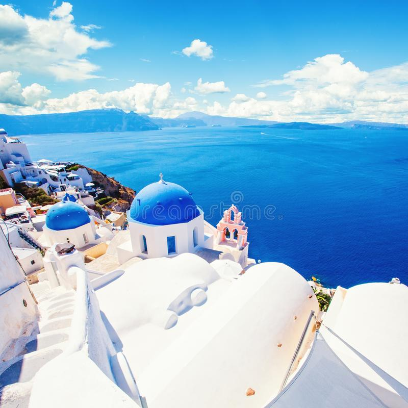 Santorini church and white houses against blue sky with clouds. Beautiful Oia village, Greece landmark stock photography