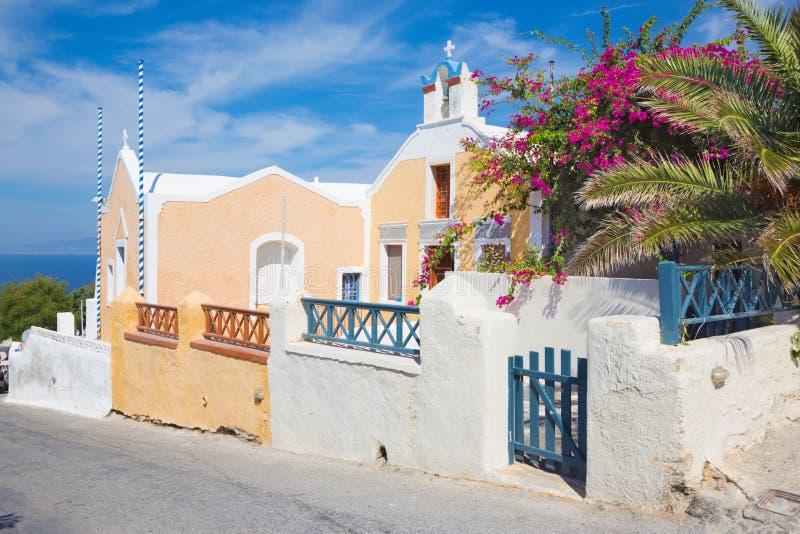 Santorini - der schöne Blick mit dem Blumen entkernten Haus und der kleinen Kirche in Oia stockfotografie