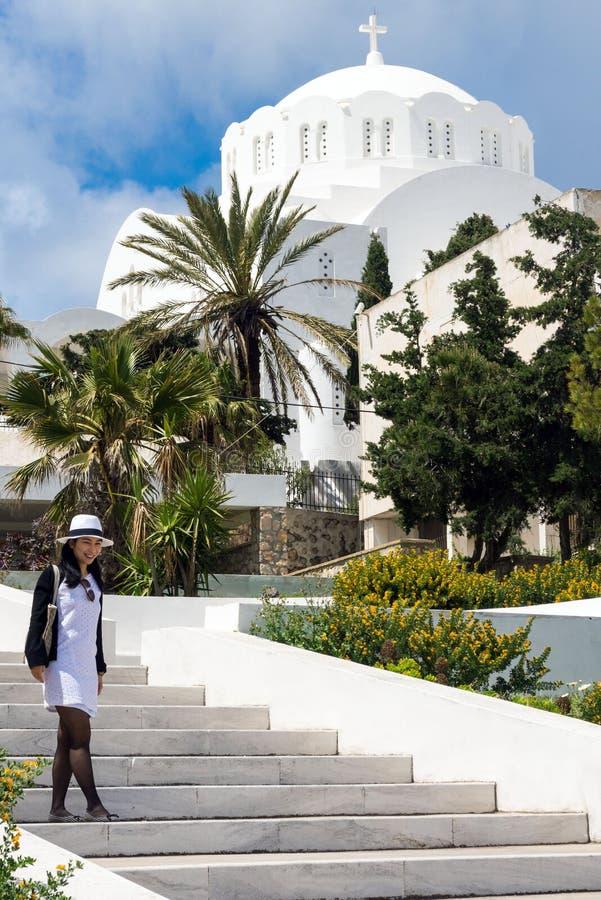 Santorini, Grecia, aprile 2019 Una ragazza in un vestito ed in un cappello bianchi è fotografata contro lo sfondo di un churc gre fotografia stock