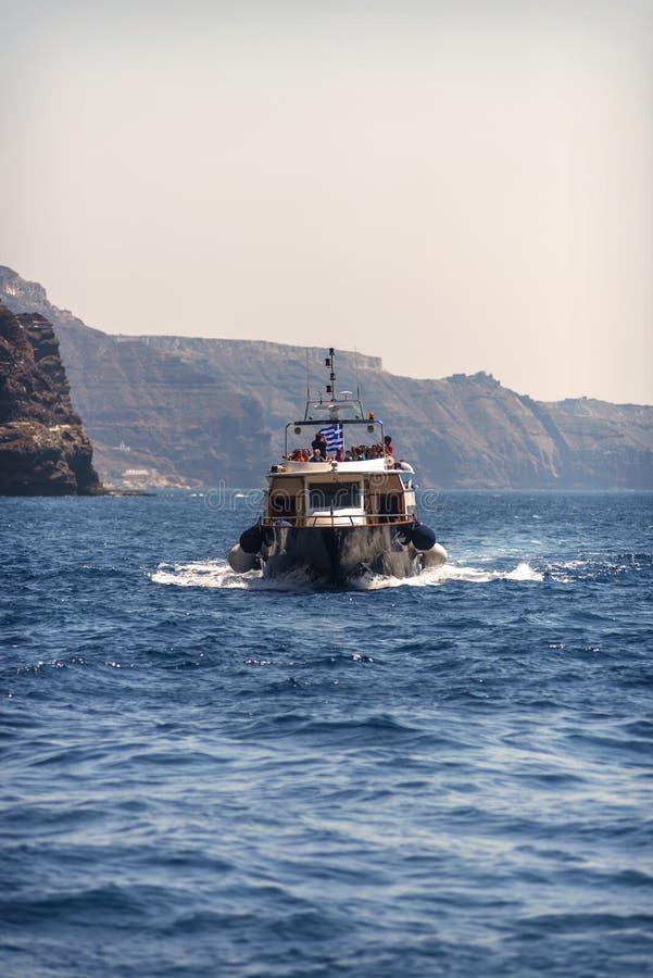 SANTORINI, GRECIA - 30 DE JUNIO: Naves turísticas en el puerto en Ju imagen de archivo