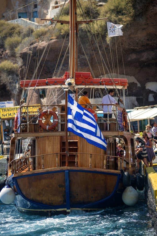 SANTORINI, GRECIA - 30 DE JUNIO: Naves turísticas en el puerto en Ju imagenes de archivo