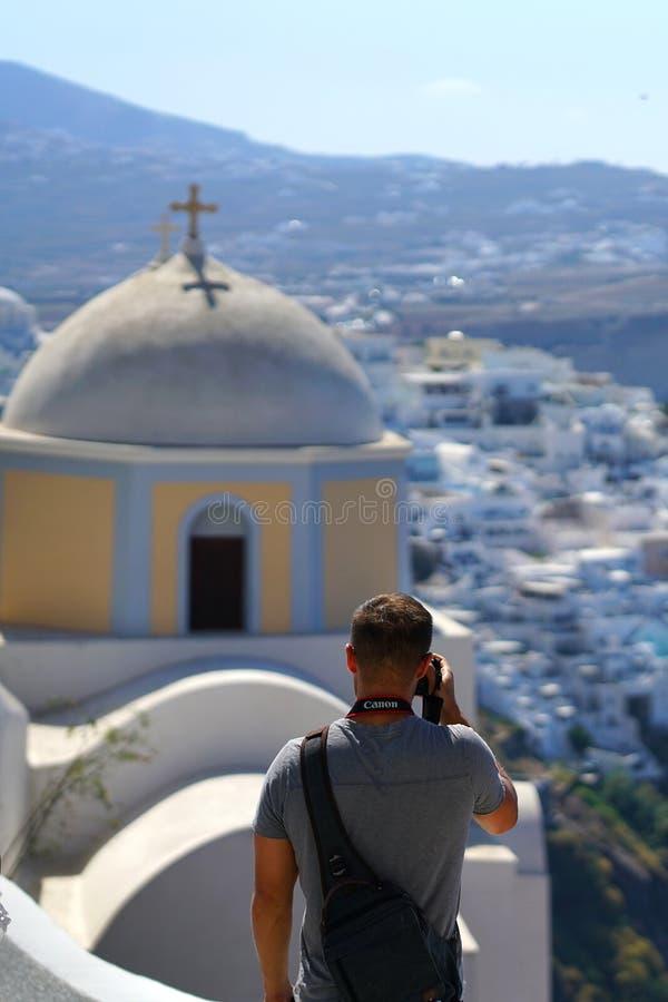 Santorini, Grecia, el 21 de septiembre de 2018, el turista masculino toma las fotografías en Thira imagen de archivo libre de regalías