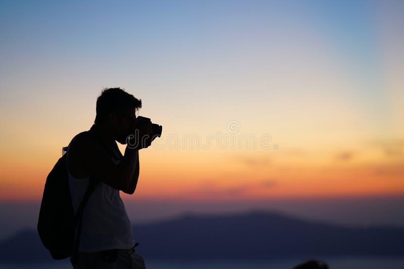 Santorini, Grecia, el 21 de septiembre de 2018, un turista se relaja tomando las fotografías de la puesta del sol imágenes de archivo libres de regalías