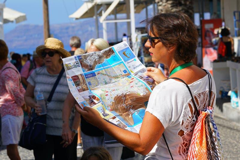 Santorini, Grecia, il 21 settembre 2018, un turista esamina una mappa fotografia stock libera da diritti