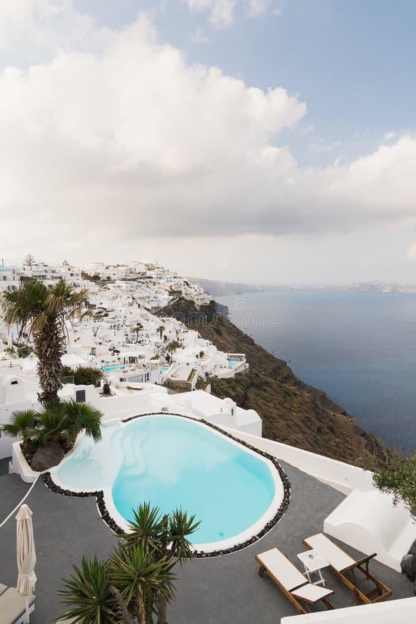 SANTORINI, GRECIA - MAGGIO 2018: Vista sopra il villaggio di Firostefani, del mar Egeo e la caldera del vulcano con l'albergo di  fotografia stock libera da diritti