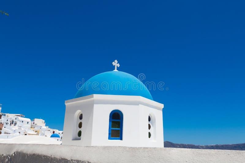 Santorini, Grecja: Błękitna kopuła kościół w w górę wyspy Santorini Tło bielu domy i błękitny morze fotografia royalty free