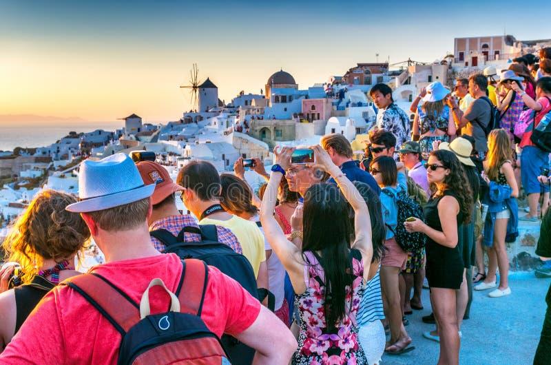 SANTORINI GRECJA, LIPIEC, - 12, 2014: Turyści cieszą się zmierzch w Oia fotografia royalty free