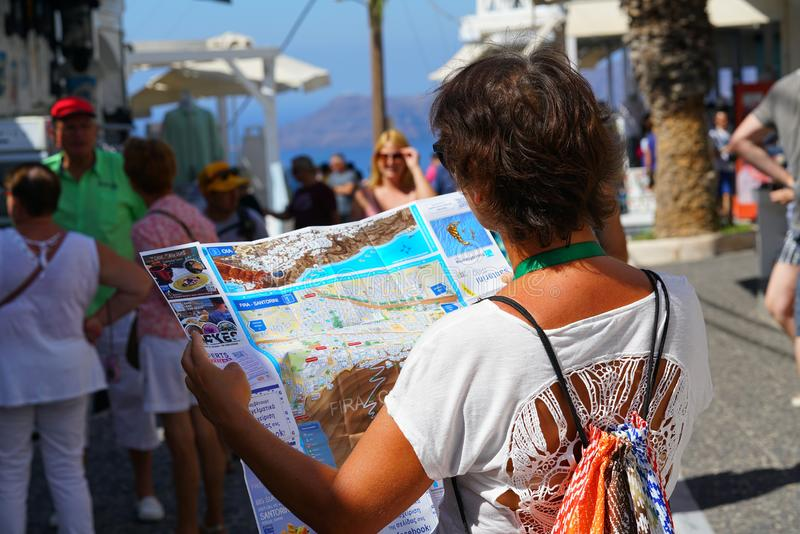 Santorini, Grecja, Wrzesień 21 2018, A turysty spojrzenia przy mapą obraz royalty free