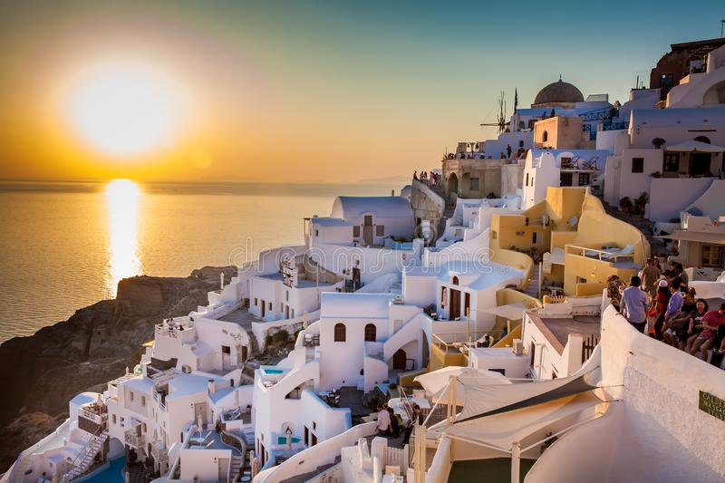 Tourists looking at the amazingly beautiful sunset at La Caldera in Oia city in Santorini Island royalty free stock photos