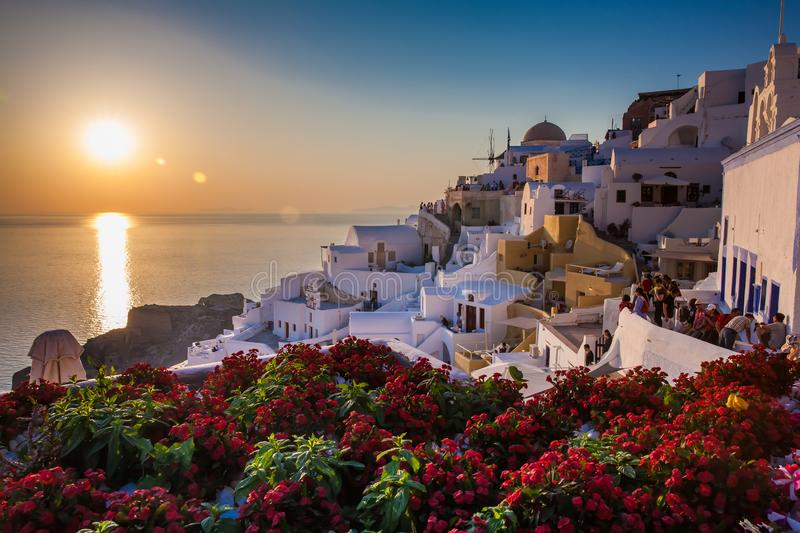 Tourists looking at the amazingly beautiful sunset at La Caldera in Oia city in Santorini Island stock photography