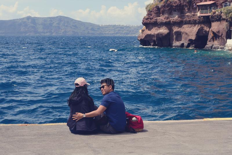 A young Chinese couple in love is sitting in the old port of the Greek city of Fira on the island of Santorini. royalty free stock photo