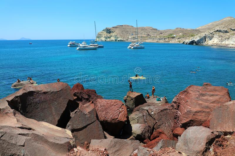SANTORINI, GREECE - JULY 21, 2018: bathers dives at Red beach in volcanic island of Santorini, Greece.  stock photos