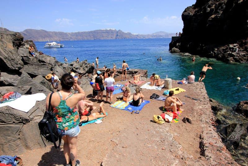 Santorini, Greece, June 15th, 2018: Tourists sunbathing on Amoudi Bay beach, Santorini, Greece. Santorini, Greece, June 15th, 2018: Tourists sunbathing on the royalty free stock images