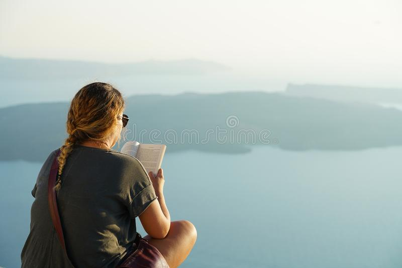 Santorini, Greece, September 21 2018, Tourist relax reading a book in the sunset royalty free stock image