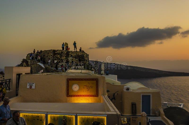 SANTORINI GREKLAND - Oktober 9, 2014: Solnedgång i byn av Oia royaltyfria bilder
