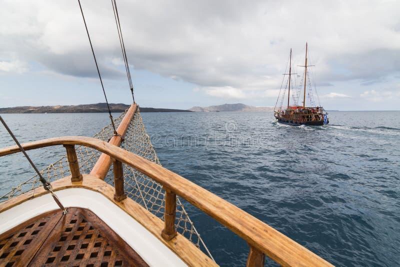 SANTORINI, GRIECHENLAND - MAI 2018: Alte hölzerne Schiffe, die in Mittelmeer in Richtung zum Vulkankessel segeln stockfotos