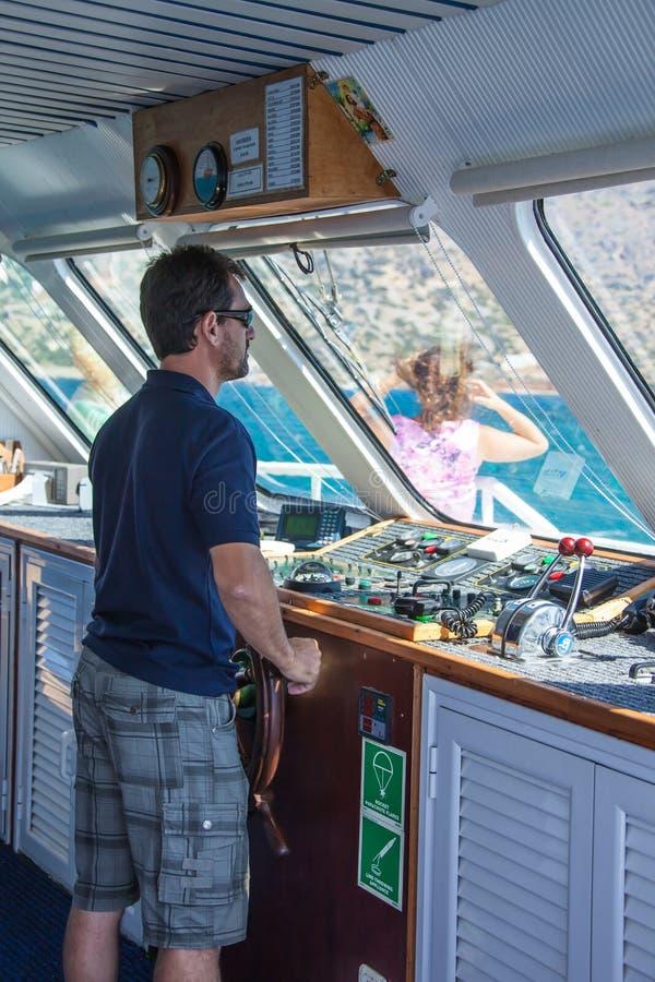 SANTORINI/GRIEKENLAND - 4 JULI 2012: de kapitein, in de werkplaats, stuurt het schip. stock afbeeldingen