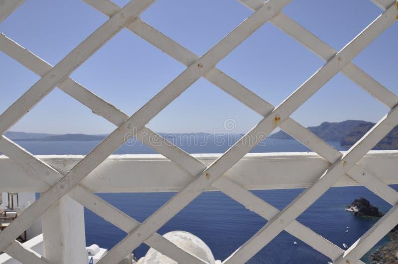 Santorini, il 2 settembre: Vista sul mare con la caldera di Santorini attraverso una griglia di legno dalla città pittoresca Fira fotografia stock
