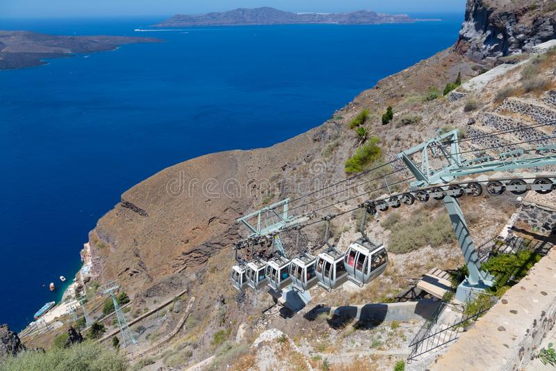 Santorini, Kreta, Griekenland: Eiland Thira, Santorini Weergeven van de vulkaan Kabelkabelbaan tegen een blauwe hemel en stock foto's