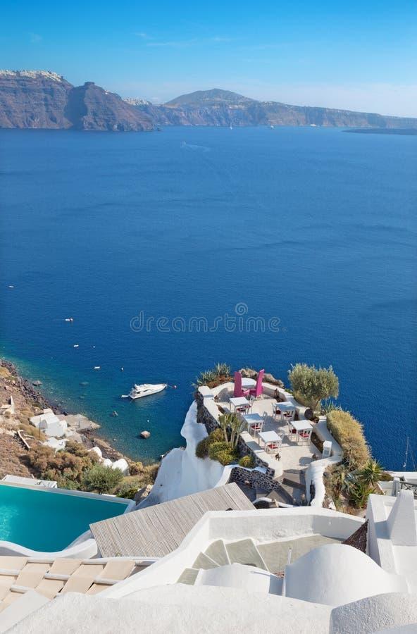 Santorini - le restaurant adapté à épouser le wagon-restaurant romantique à Oia Ia et le yacht sous des falaises à l'arrière-plan photographie stock libre de droits