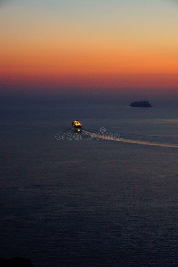 Santorini Magic Island in Greece. Nave da crociera in partenza dalla caldera di Santorini in Grecia, all`ora del tramonto, verso un viaggio nel Mediterraneo stock image