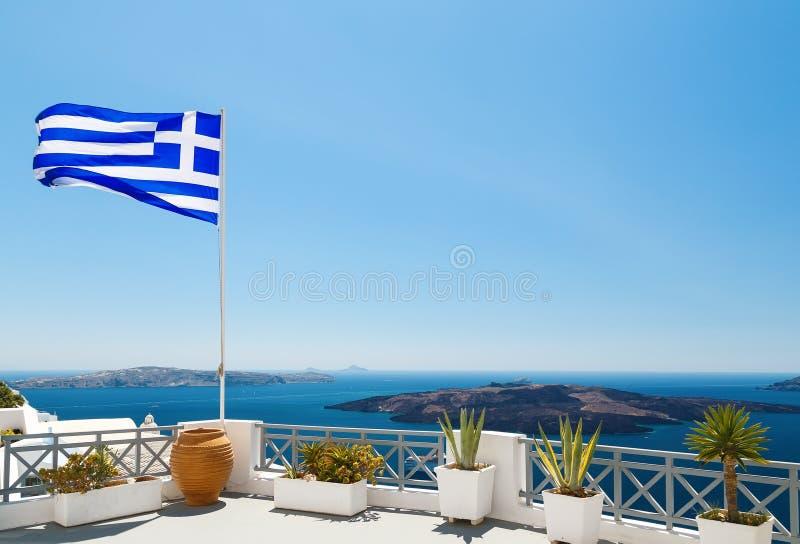 Santorini met vlag op wit balkon van hotel met bloemen en potten van Griekenland, de hoofdstad van Fira royalty-vrije stock fotografie