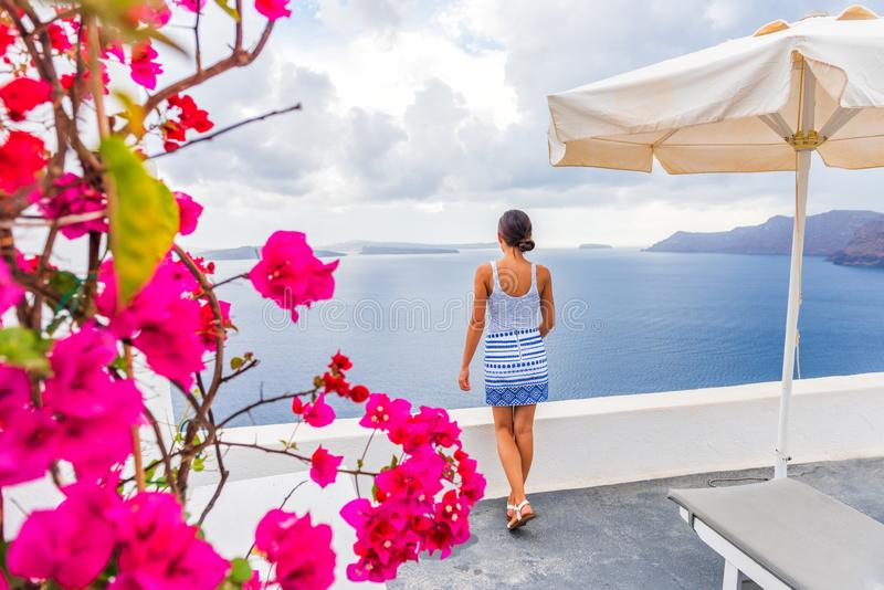Santorini Oia hotel luxury resort tourist woman looking at view from balcony - Greece summer travel vacation. Santorini Oia hotel luxury resort holiday tourist royalty free stock photo