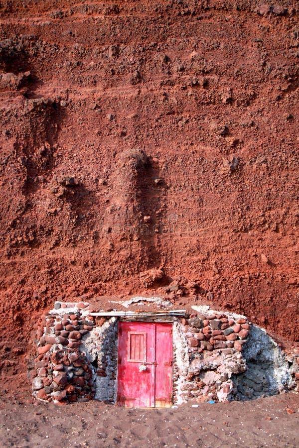Santorini. Playa roja de la arena. Casa de piedra de la lava imágenes de archivo libres de regalías