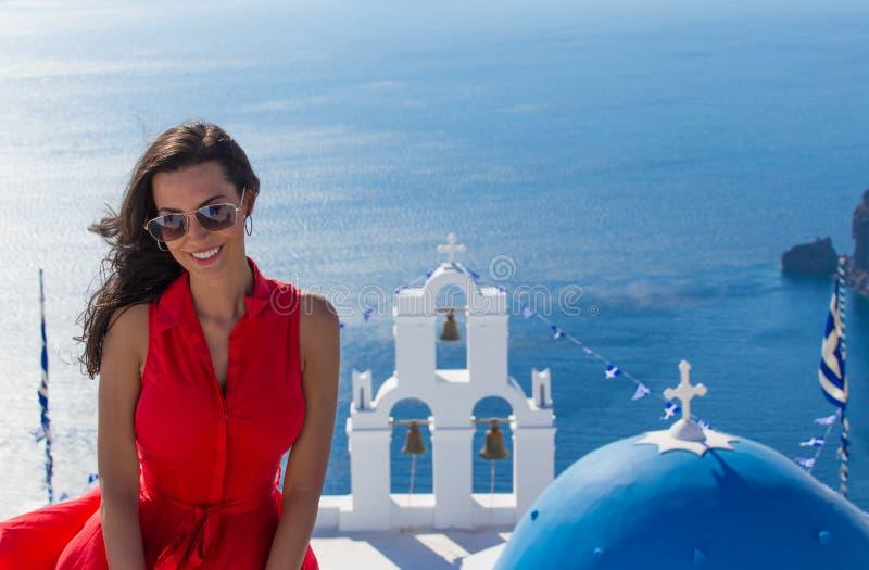Santorini podróży brunetki turystyczna kobieta w czerwieni Fira smokingowym odwiedza mieście zdjęcie stock