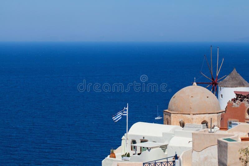 Santorini-Skyline mit griechischer Flagge, Meer, blauem Himmel und Stadt Griechenland-Markstein stockfotos