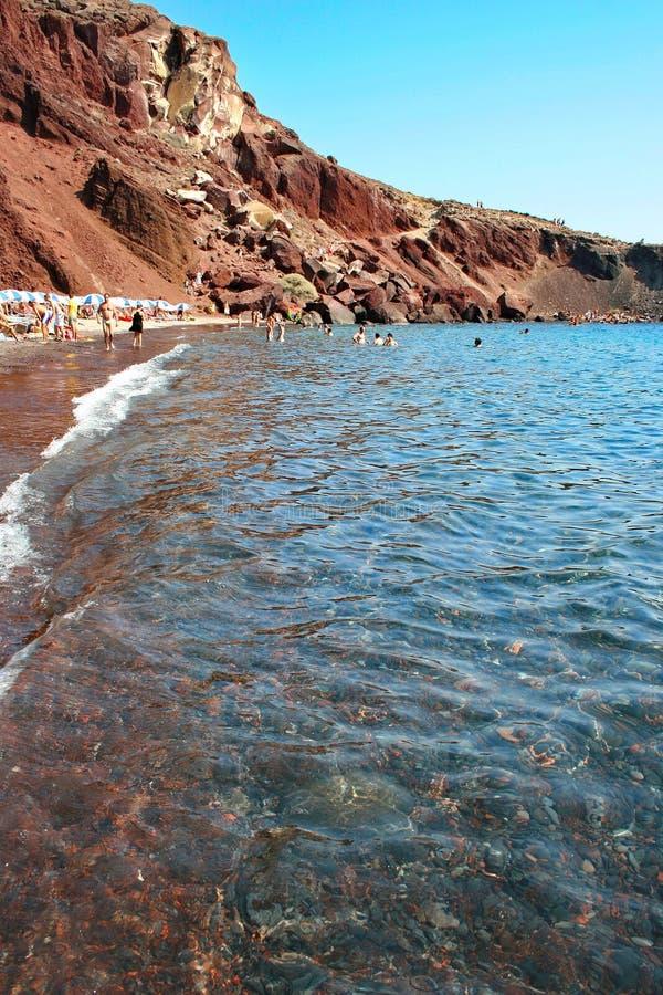 Santorini: Turister på den röda stranden, en av dess mest berömda och mest härliga stränder royaltyfri foto
