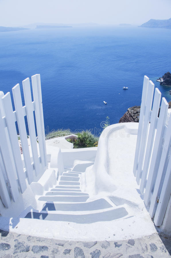 Santorini. White fence leading to the blue sea in Santorini stock images